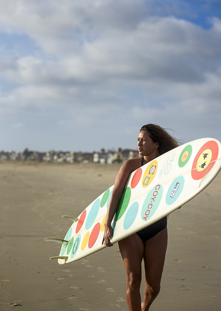 Surfer Vanessa Yeager, 32, walks with her longboard along the shore at Newport Beach, Calif.