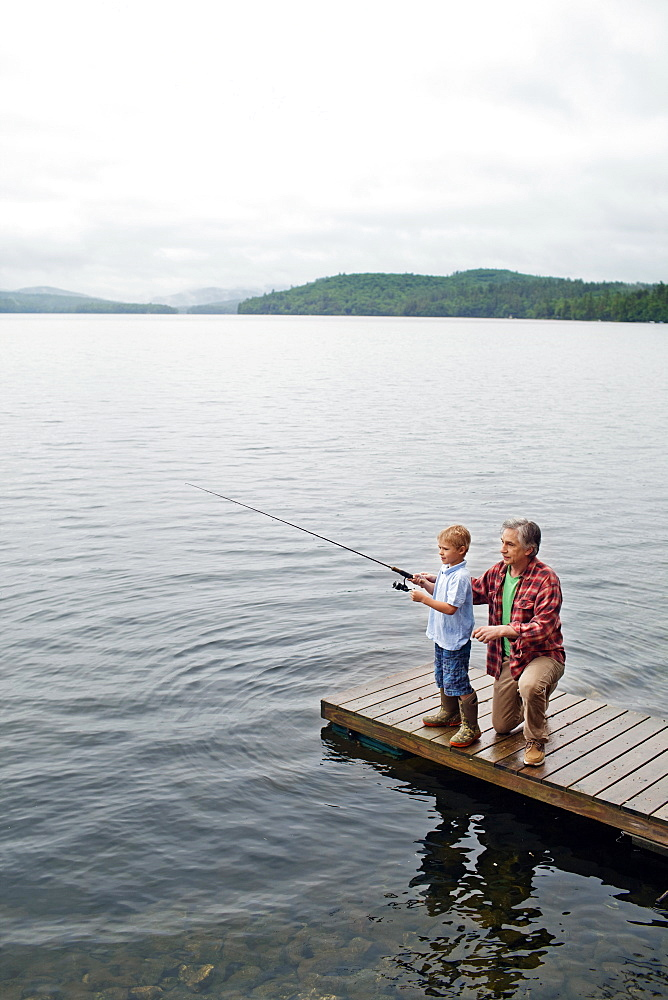 Senior man showing grandson how to fish off dock at Kezar Lake