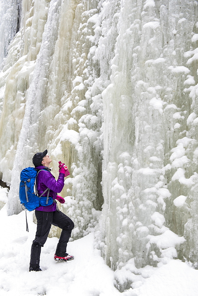 A woman hiker looking up at a tall wall of ice and snow. - 857-93059