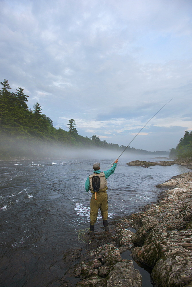 Rear View Of A Fly Fisherman Fishing At Kennebec River, Maine