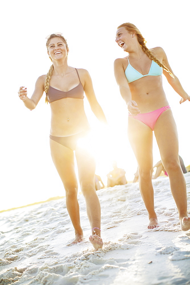 Two Female Friends Laughing And Walking On Beach