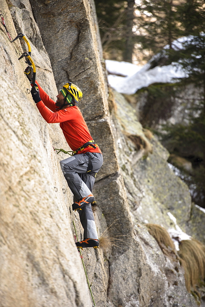 Male Climber Ice Climbing And Drytooling In Ceresole Reale Ice Park