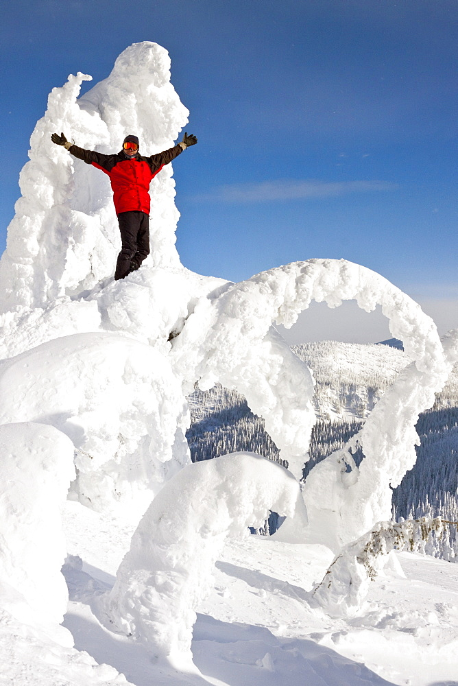 Male Snowboarder Standing On Snow Shaped Ghost At Whitefish, Montana, Usa