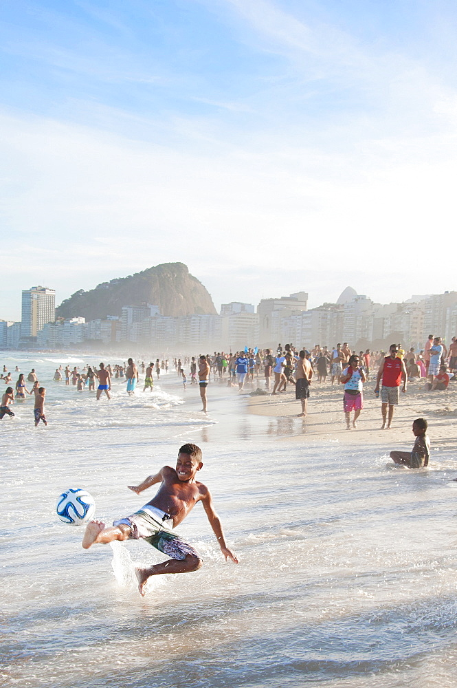 A Little Boy Kicks A Soccer Ball In The Surf Of Copacabana Beach, Rio De Janeiro, Brazil