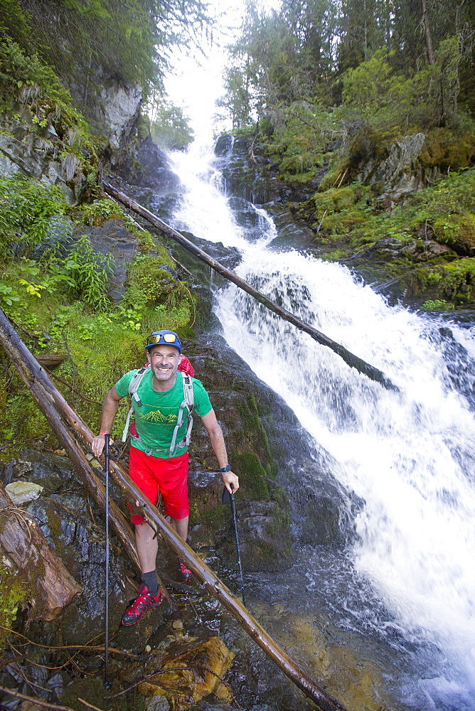 A Male Hiker Is Soaking Wet After Traversing A River With A Waterfall In The Val Danniviers