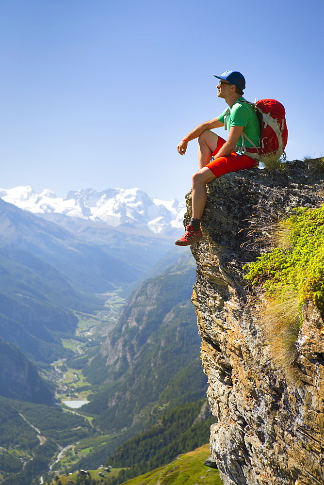 A Hiker Is Taking A Rest At A Steep Rock Face  Above The Matterhorn Valley