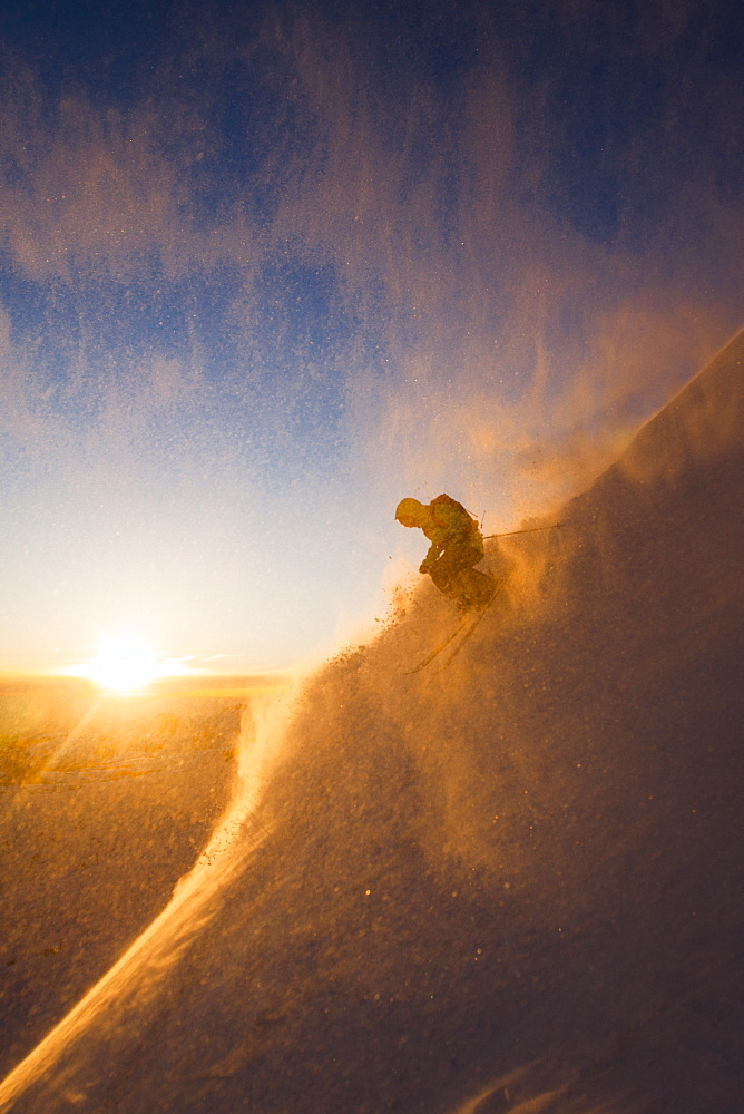 Bryce Philips Surrounded By Snow Powder During Skiing On Snowy Landscape During Sunset