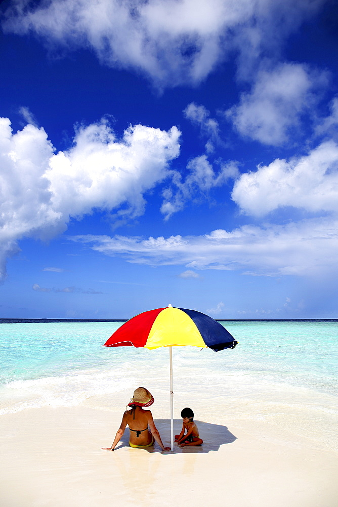 Mother And Child Relaxing On The Beach Of Maldives Island Of Gulhi