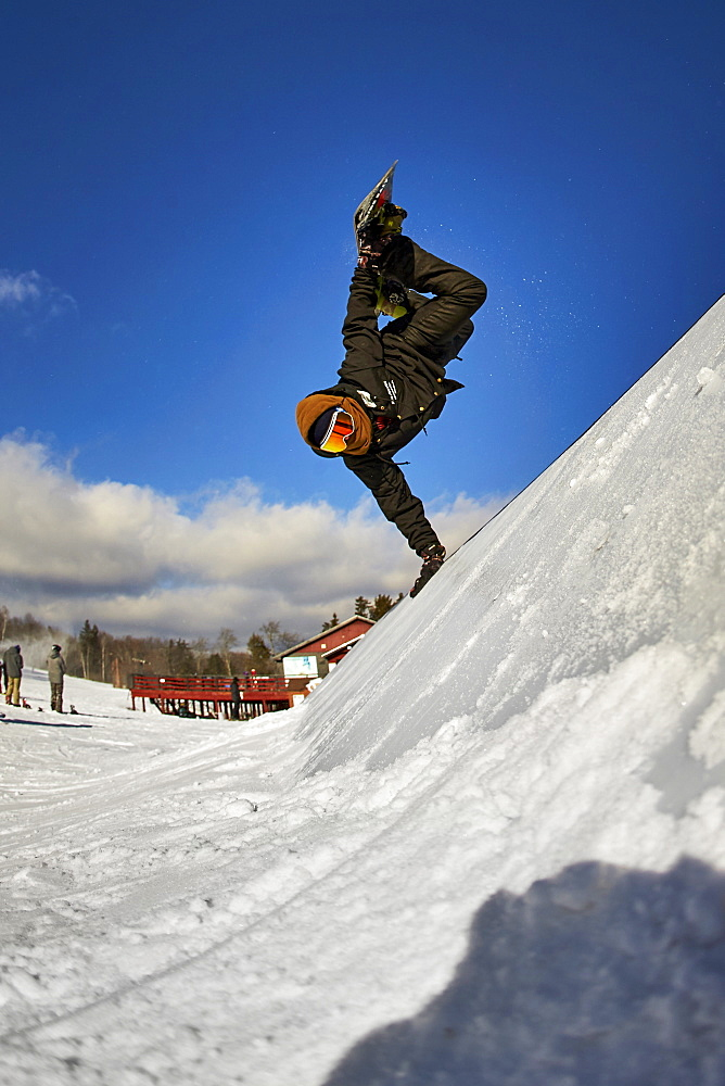 A snowboarder doing a handplant on a feature in the terrain park.