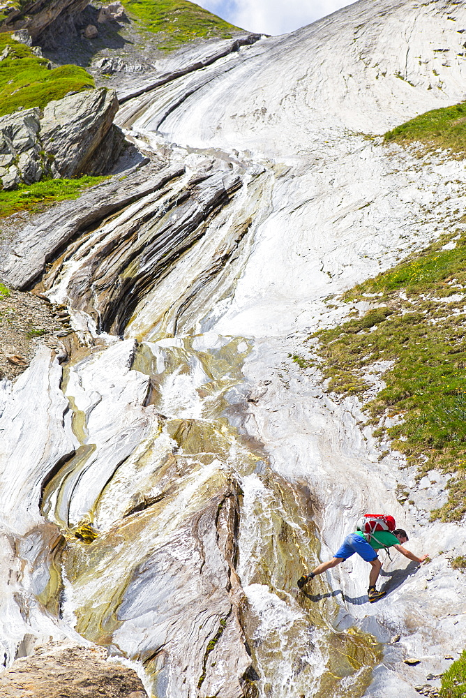 A hiker is scrambling on a spectacular rock formation near the Col des Fours above la Ville des Glaciers. This is halfway the Tour du Mont Blanc, a classic trekking around the highest peak of the Alps, that goes through France, Italy and Switzerland.