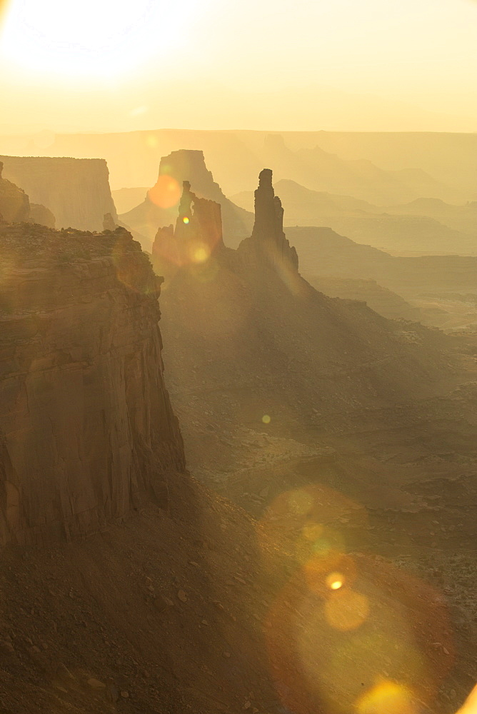An orange sun beam cuts through rock formations in Canyonlands National Park in Moab Utah at sunrise.