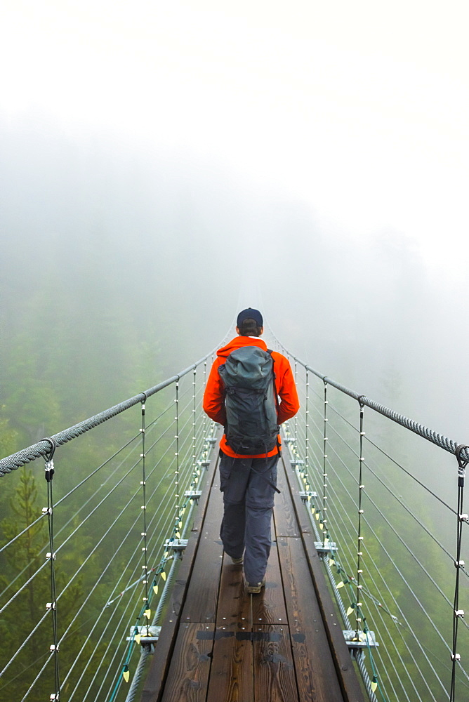 A man walks across a suspension bridge on a rainy fall day in Squamish, British Columbia.