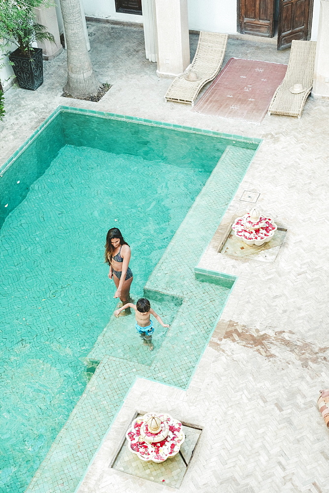 High angle view of mother in bikini with son in swimming trunks in swimming pool in Moroccan riad, Marrakech, Morocco