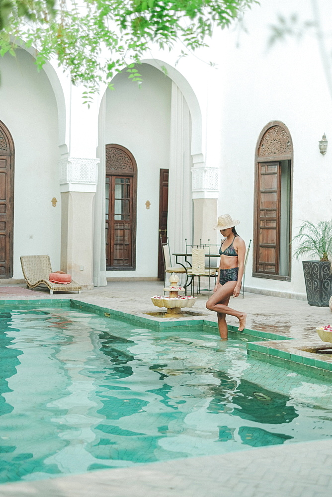 Woman in bikini walking into swimming pool in Moroccan riad, Marrakech, Morocco