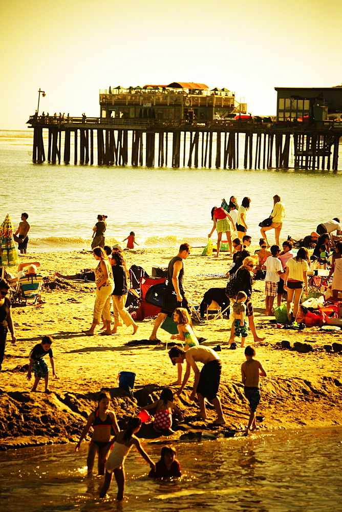 People at play on the beach in Capitola. Sepia and yellow toned.