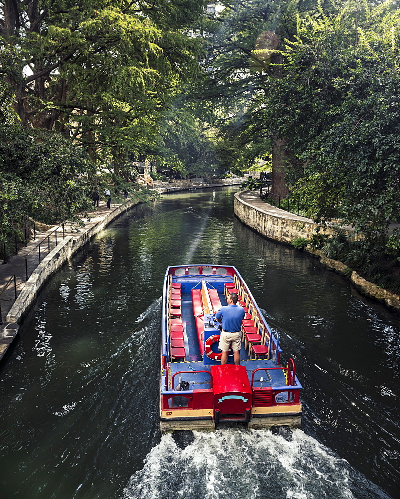 A man drives a water taxi along the San Antonio river walk on a sunny late summer day. The riverwalk is covered with a canopy of trees and makes for a nice peaceful place to walk.