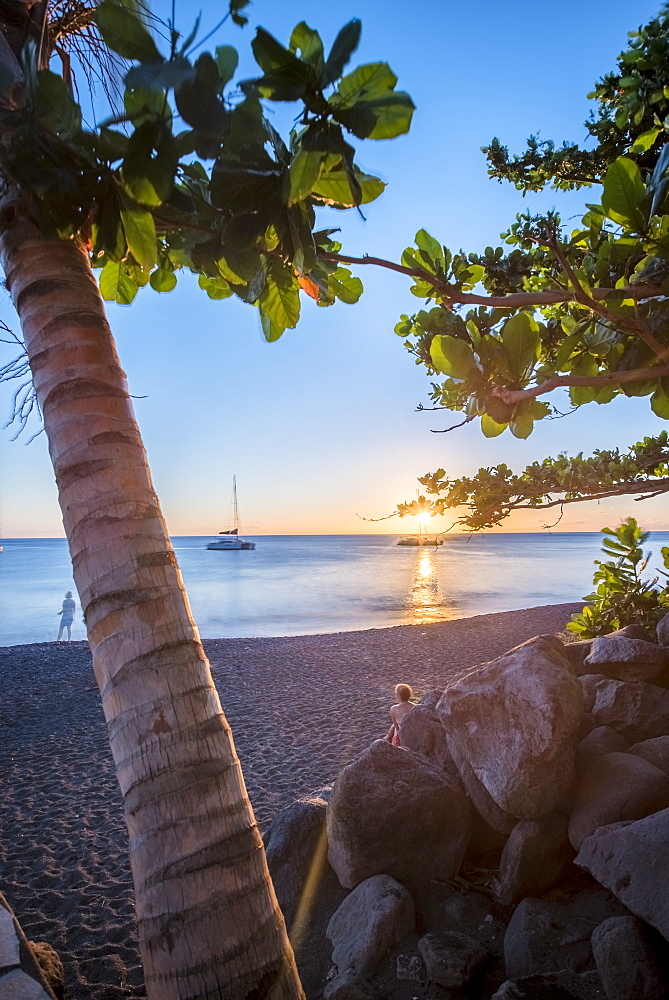 View of beach at sunset with palm trees, tourists and sailboat in distance, Black Sand Beach, Basse Terre, Guadeloupe