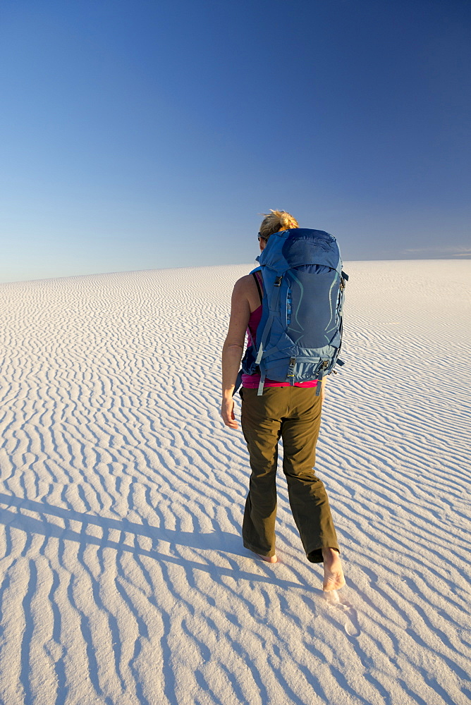 Rear view of female backpacker hiking in desert of White Sands National Monument, Alamogordo, New Mexico, USA