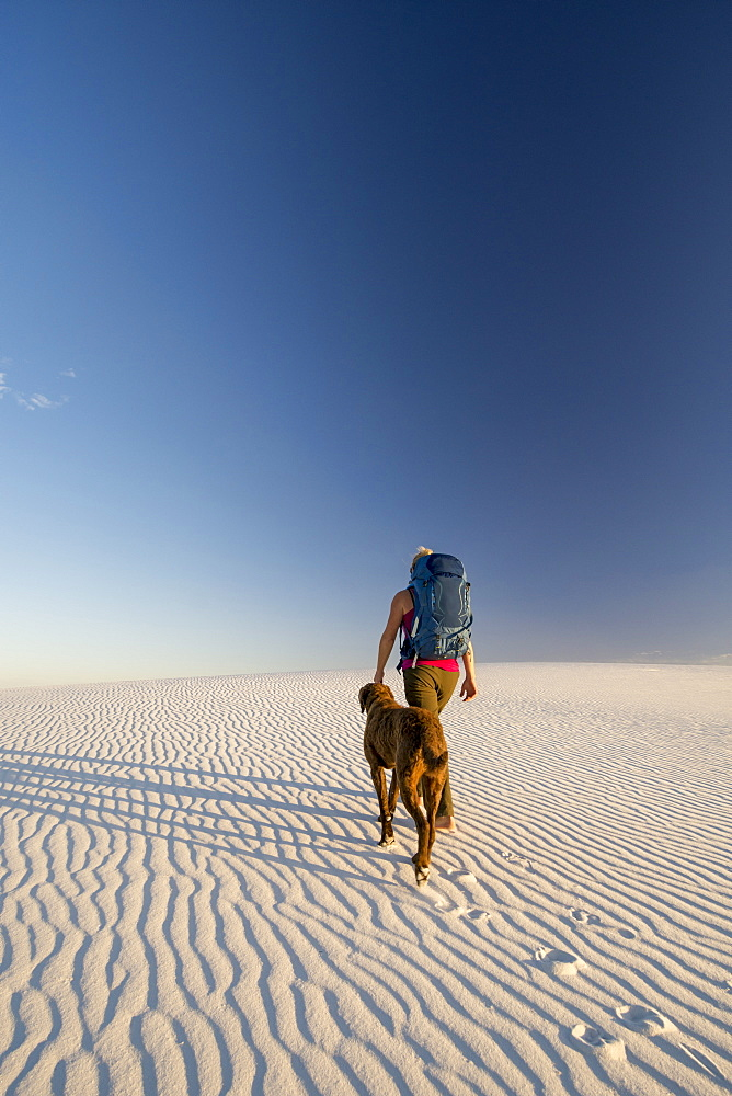 Rear view of female backpacker with dog hiking in desert of White Sands National Monument, Alamogordo, New Mexico, USA