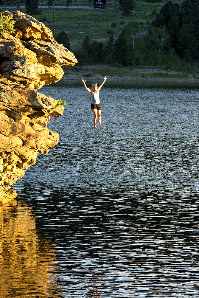 Adventurous woman jumping off rock into lake, Estes Park, Colorado, USA
