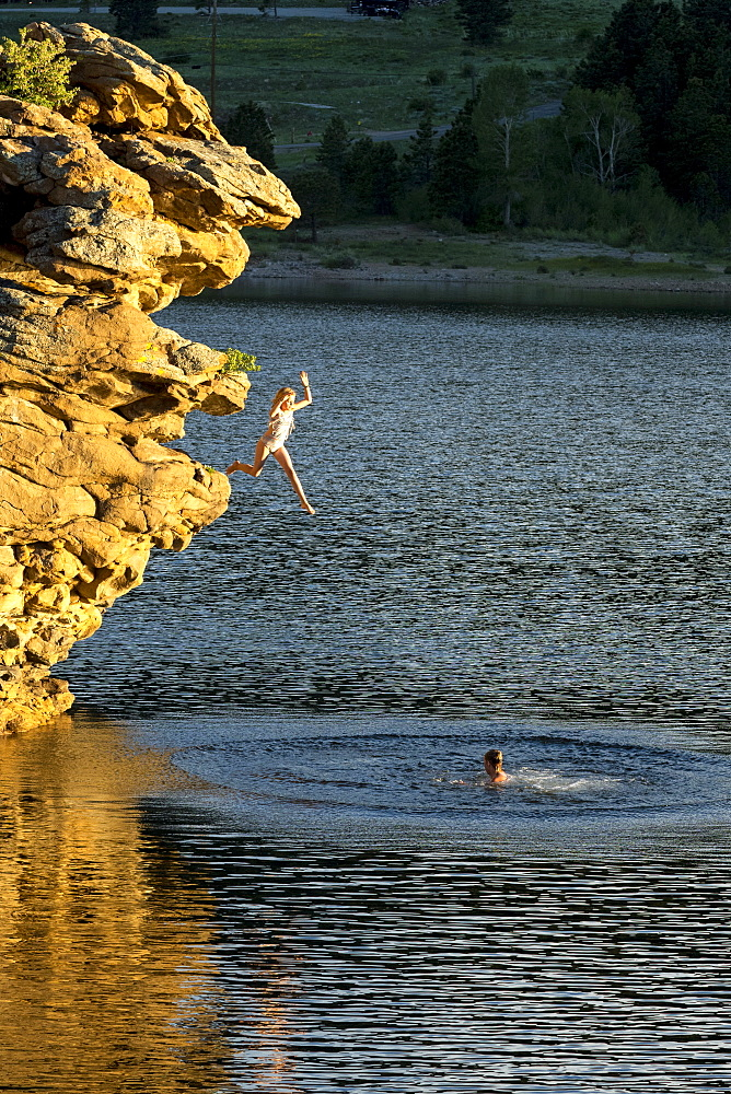 Adventurous girl jumping off rock into lake, Estes Park, Colorado, USA