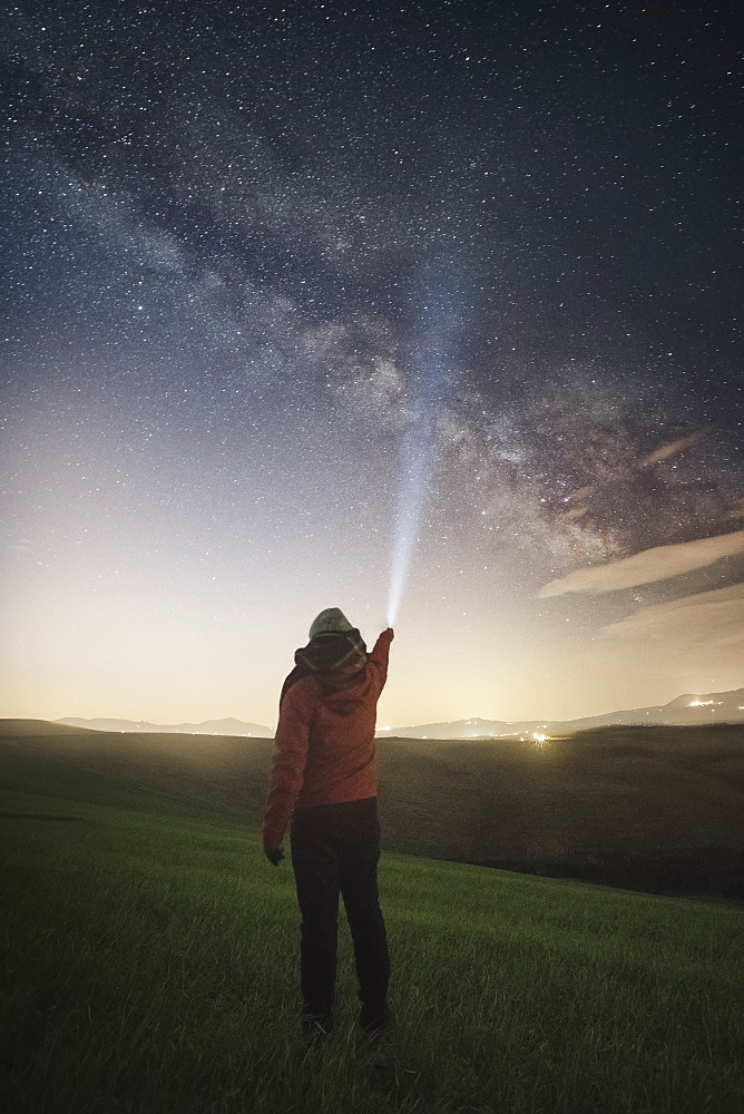 Milky Way galaxy and stars in sky above man shining flashlight at sky at dusk