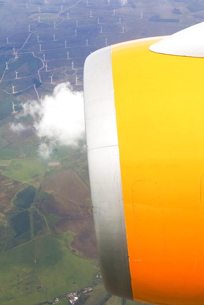 Jet engine of airplane flying over wind farm, Scotland, UK