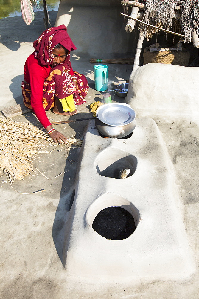 A woman subsistence farmer cooking on a traditional clay oven, using rice stalks as biofuel in the Sundarbans, Ganges, Delta, India. the area is very low lying and vulnerable to sea level rise. All parts of the rice crop are used, and the villagers life is very self sufficient, with a tiny carbon footprint.