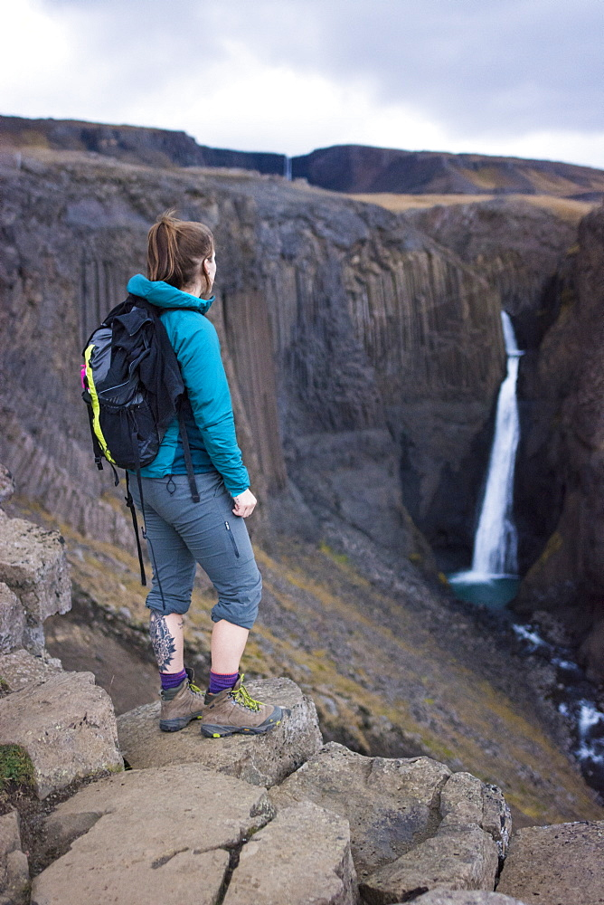 Female backpacker standing on rocks and looking at distant Litlanesfoss waterfall, Iceland