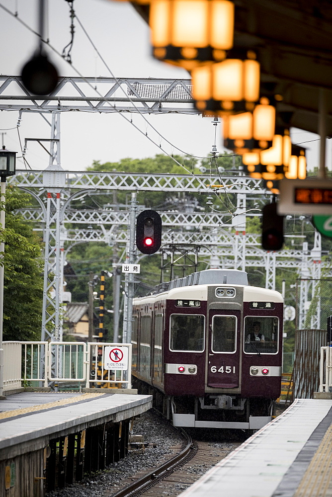 Train departing from railroad station illuminated by glowing lanterns, Arashiyama, Kyoto, Japan