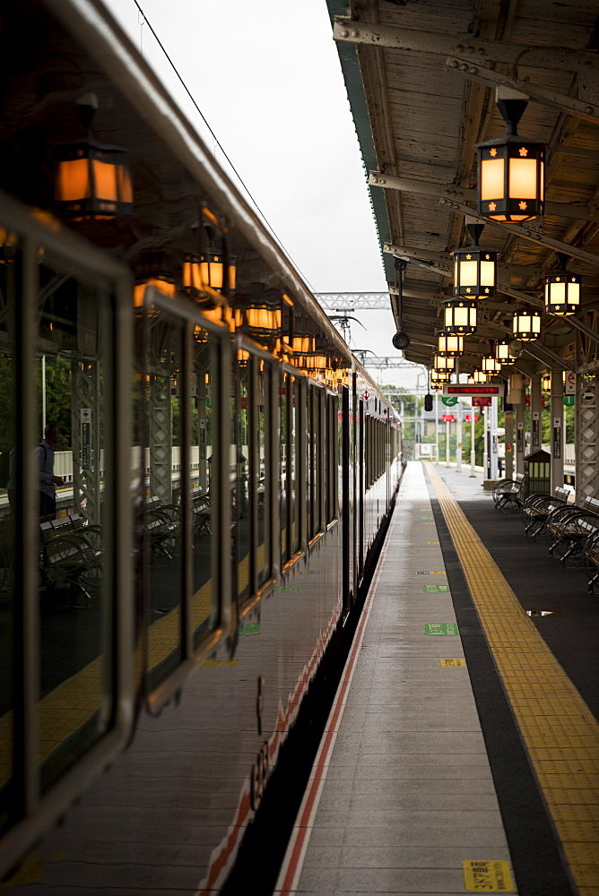 Train waiting at railroad station illuminated by glowing lanterns, Arashiyama, Kyoto, Japan