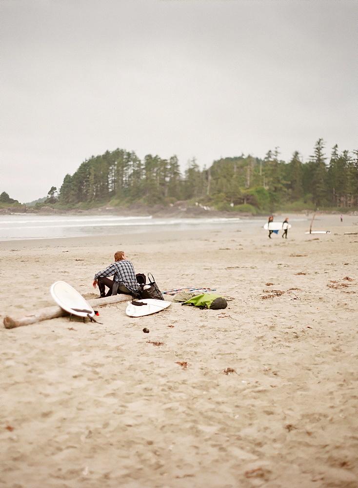 Surfer sitting on log on sandy beach, Vancouver, British Columbia, Canada
