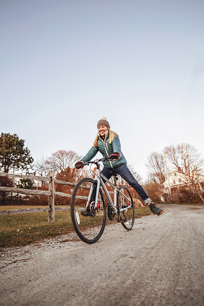 Young woman riding bicycle along countryside dirt road beside wooden fence, Portland, Maine, USA