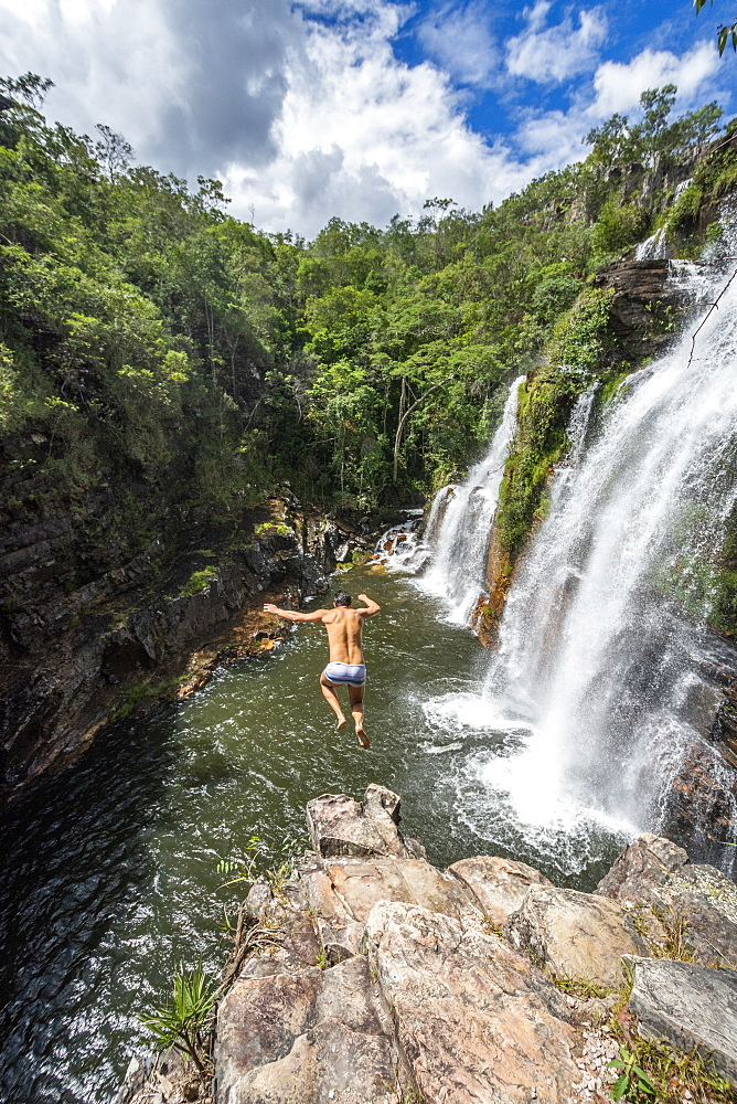 View of adventurous man cliff jumping from waterfall in cerrado, Chapada dos Veadeiros, Goias, Brazil