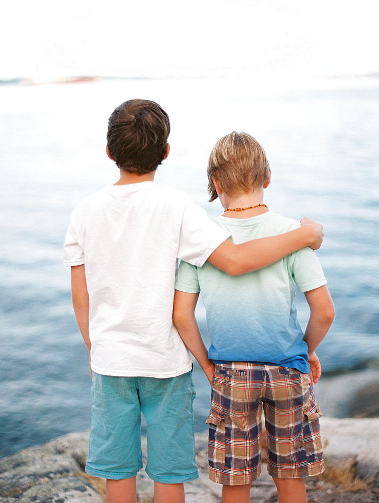 Rear view of two brothers wearing t-shirts and shorts with arm around standing against sea - 857-96074
