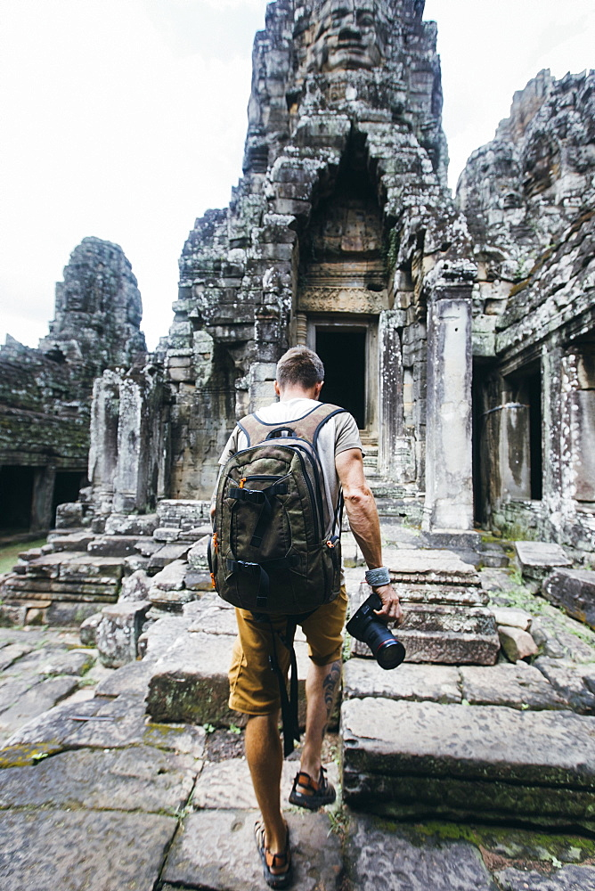 Rear view shot of a single tourist holding a camera exploring ancient Cambodian temple, Siem Reap Province, Cambodia - 857-96125