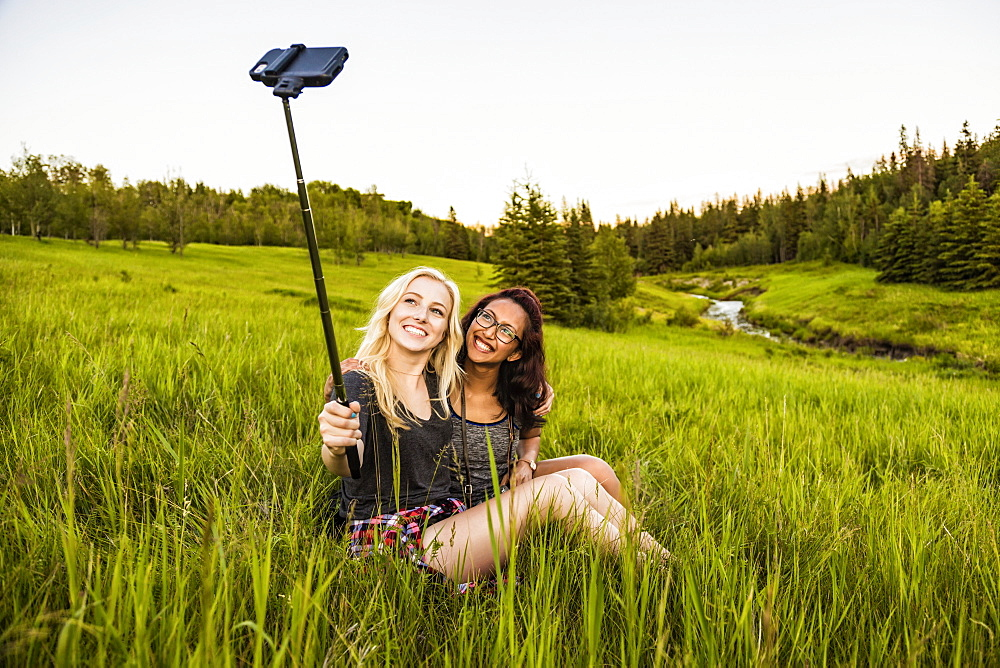 Two girlfriends sitting in a grass field posing for a self-portrait with a selfie stick and smart phone; Edmonton, Alberta, Canada