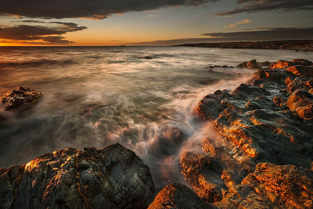 Atlantic ocean water rolls into the rocky shoreline at sunrise with a view of the coastline; Bonavista, Newfoundland, Canada