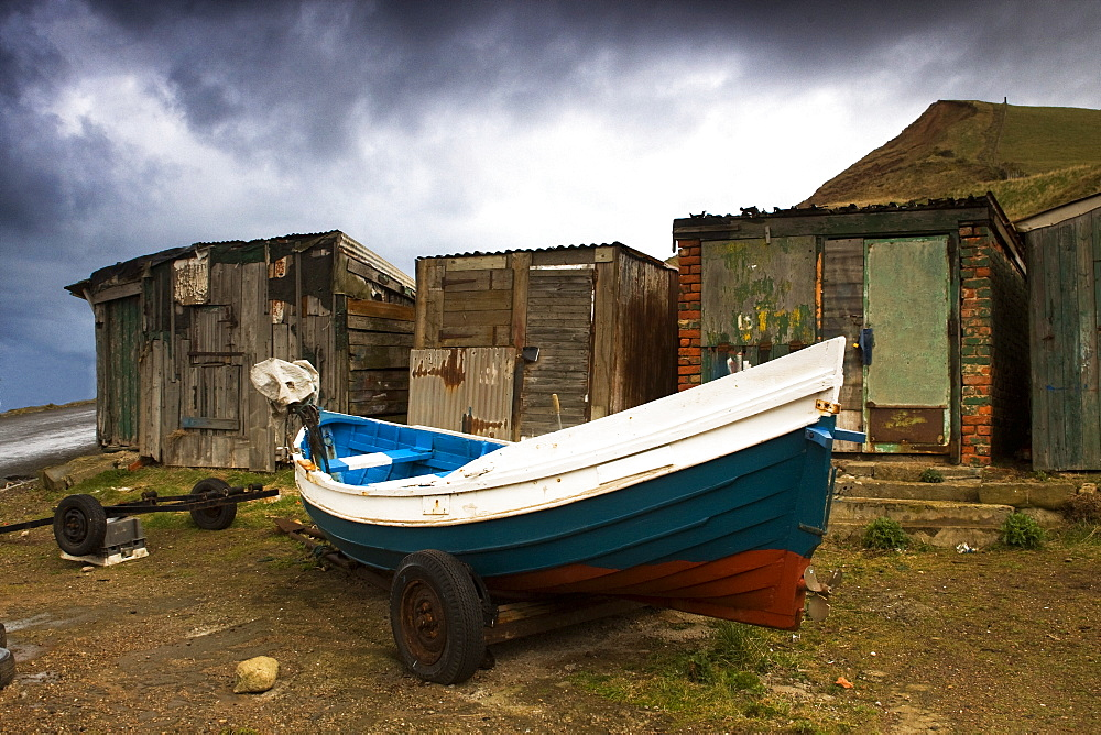 Boat Beside Old Shacks