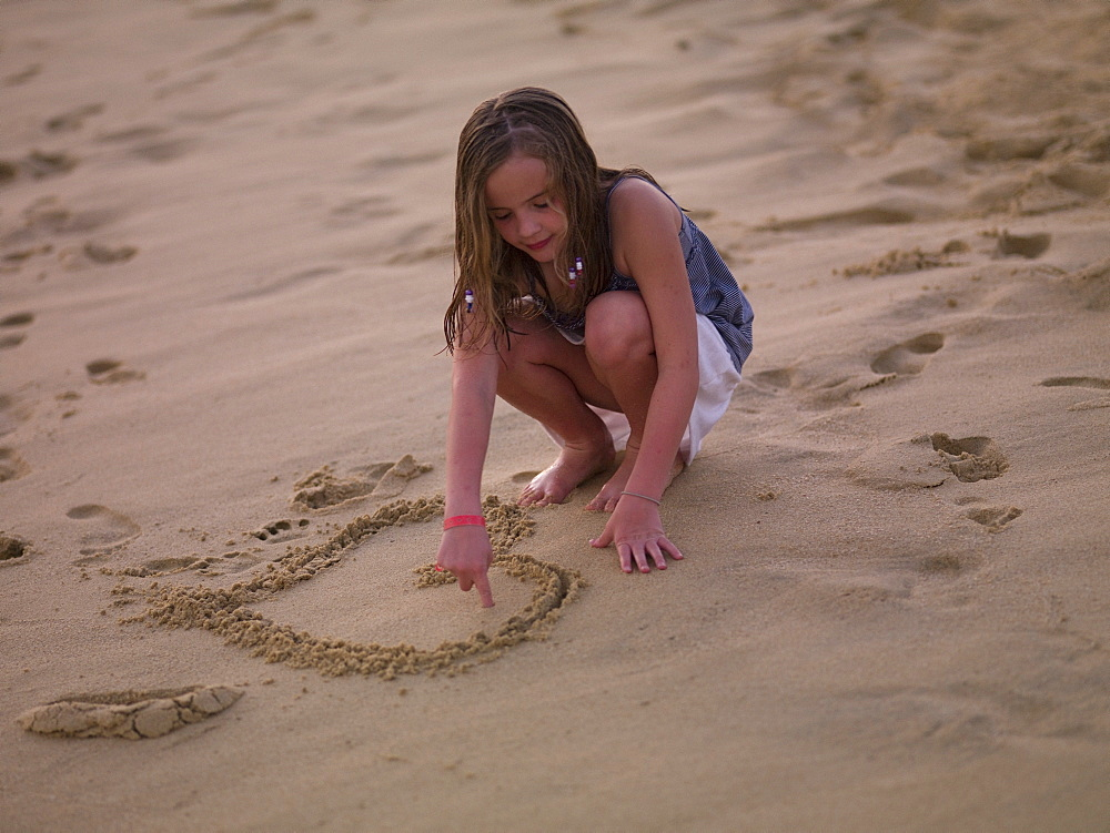 Girl Drawing Heart In The Sand