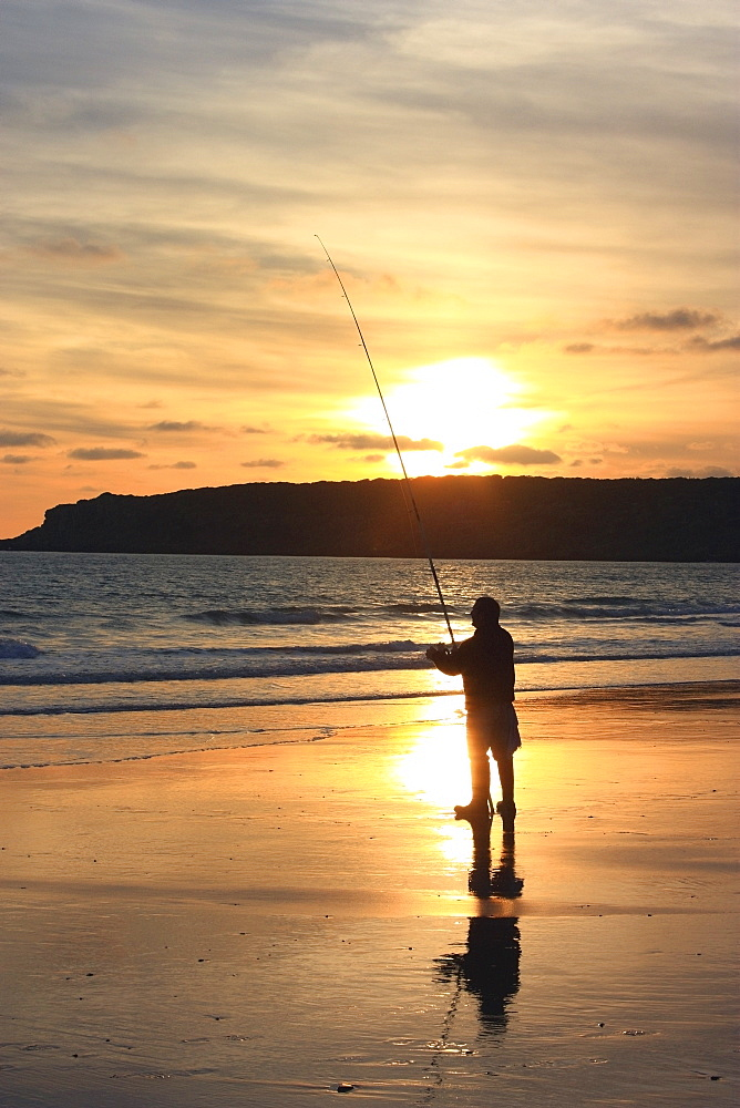 Silhouette Of Person Fishing On A Beach