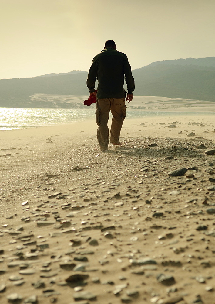 Man Walking On A Rocky Beach