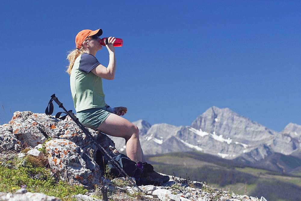 Female Hiker Sitting On A Rock Drinking From A Water Bottle