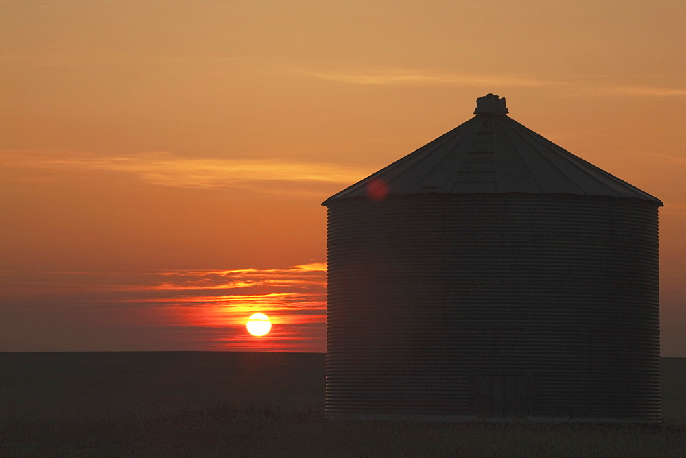 Silhouette Of Grain Bin At Sunrise