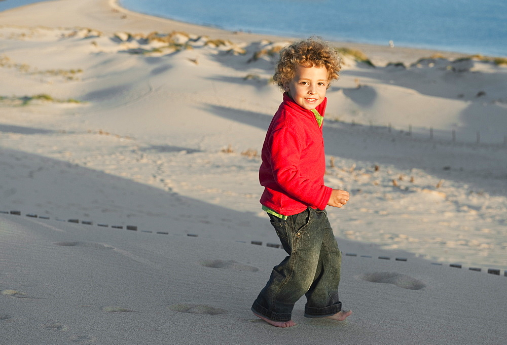 A Boy Walking In The Sand