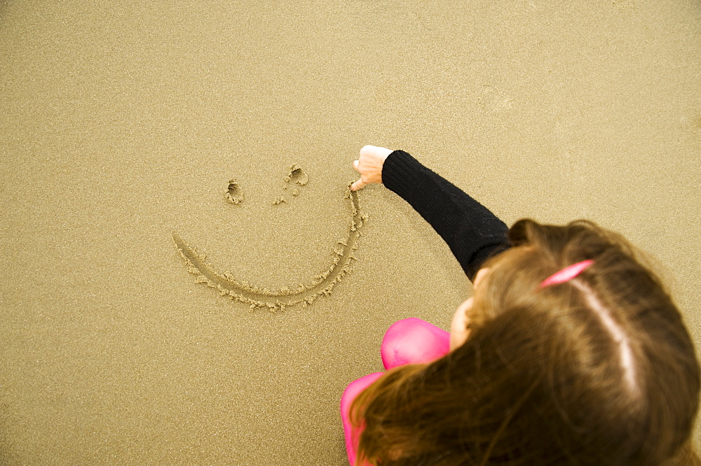 A Girl Draws A Happy Face In The Sand - 1116-41277