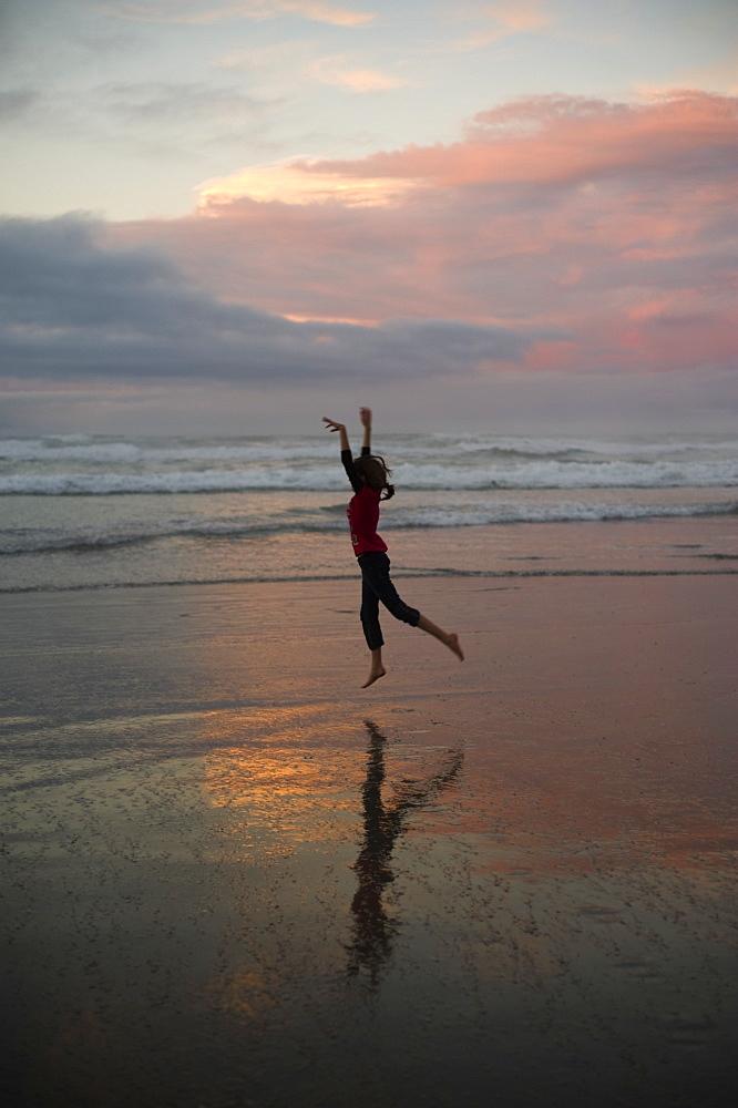 A Girl Dances On The Beach At Sunset, Waihi Beach, New Zealand