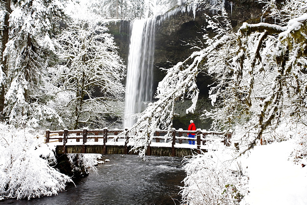 A Person Standing On A Snow Covered Bridge Watching A Waterfall In Winter