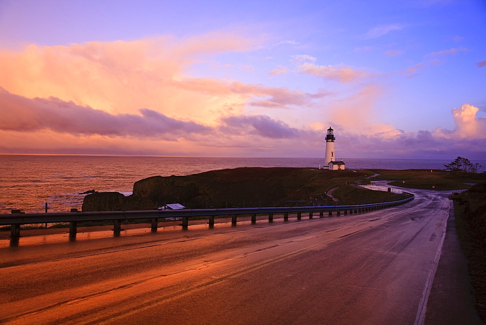 A Road And A Lighthouse Along The Coast At Sunset
