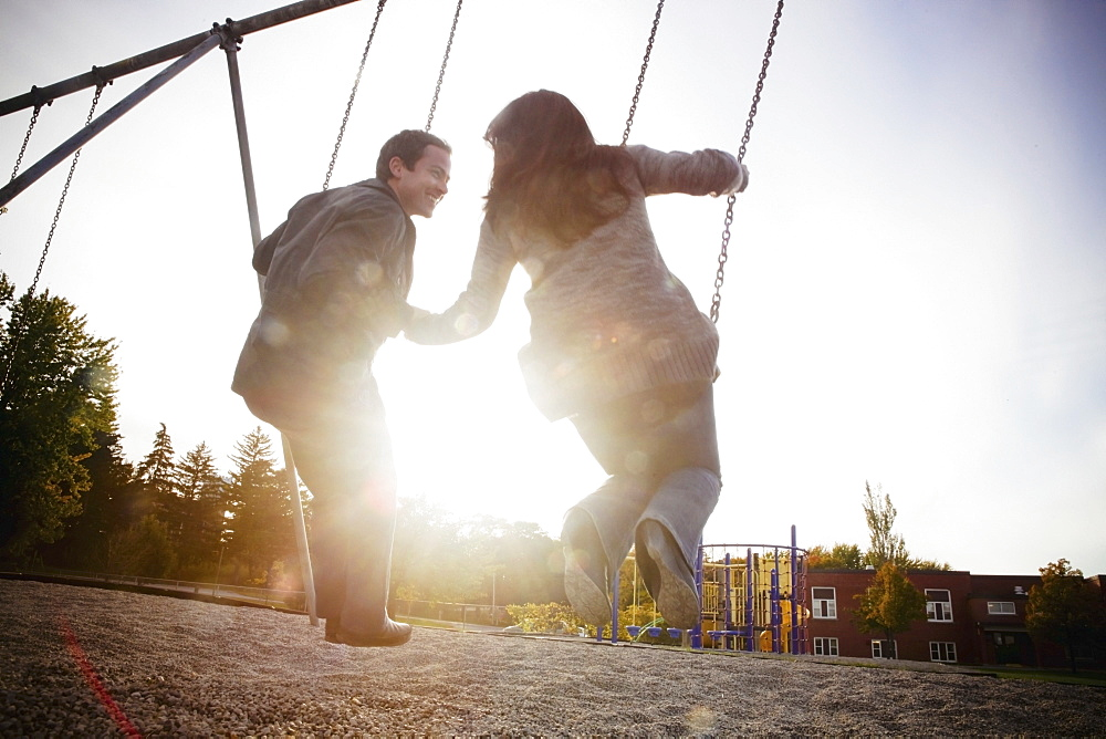 Hamilton, Ontario, Canada, A Couple On The Swings At The Playground